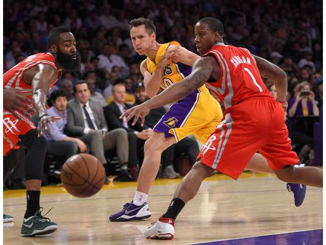 Lakers guard Steve Nash, center, passes the ball as Houston Rockets guards James Harden, left, and Isaiah Canaan defend during the first half of Tuesday's game in Los Angeles.