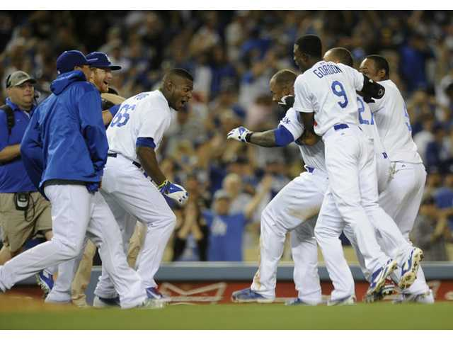 Los Angeles Dodgers' Carl Crawford, center, celebrates with teammates after beating the Detroit Tigers in Los Angeles on Tuesday.