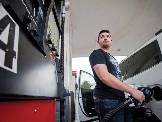 Levi Wenrich pumps gas at the Alliance gas station on Lyons Avenue in Newhall on Thursday. Signal photo by Charlie Kaijo.