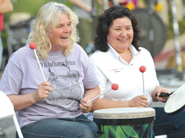 Amanda Brown of Auga Dulce, left, and Teresa Smalley of Newhall join in a drum circle at the first JAM Session Thursday night in Newhall. Signal photo by Dan Watson.