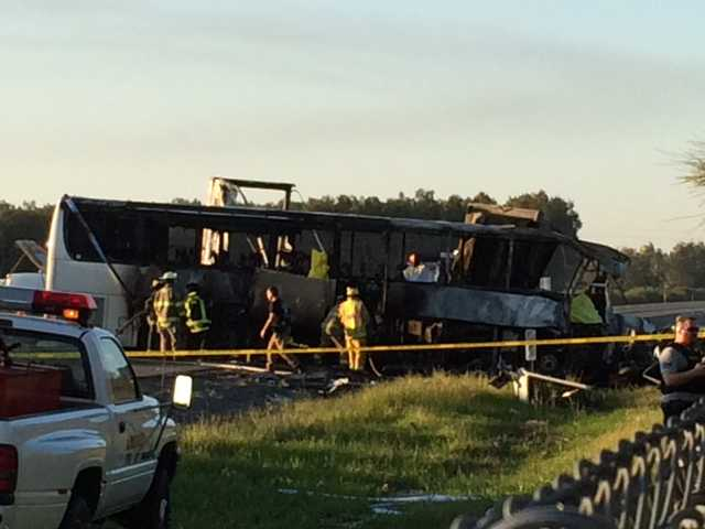 The shell of a bus sits on the side of the freeway after the crash. AP Photo/Andrew Hutchens