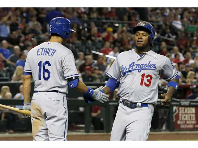 The Dodgers' Hanley Ramirez (13) shakes hands with Andre Ethier (16) after Ramirez scored a run against the Diamondbacks during the eighth inning of Friday's game in Phoenix.
