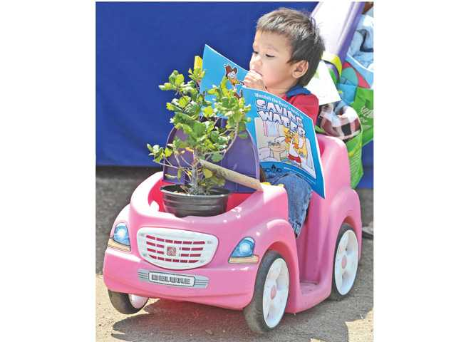 Henry Cortez, 2, of Saugus reads a coloring book on water-saving tips while his push car transports a young oak tree ready for planting as he and his family attend the City of Santa Clarita Earth Arbor Day Festival held at Central Park in Saugus on Saturday.