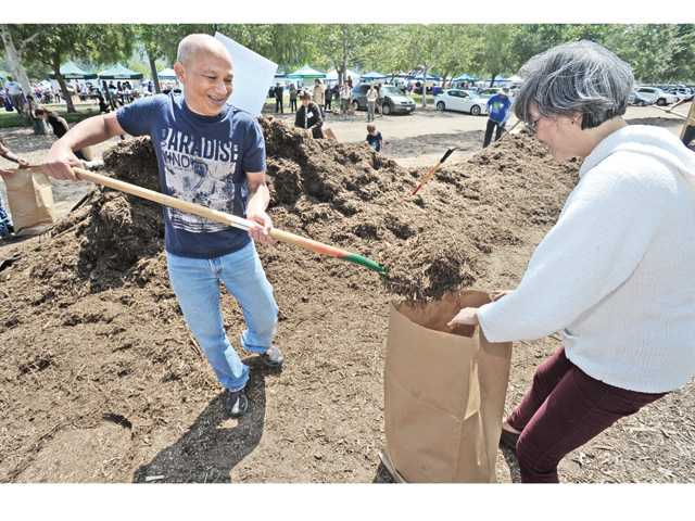 Carlos and Meylin Yi of Valencia take advantage of the free mulch on hand at the City of Santa Clarita Earth Arbor Day Festival held at Central Park in Saugus on Saturday.