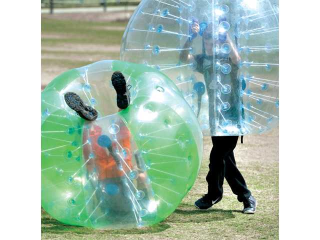 Riley Ruiz, 13, right, upends Wyatt Hoglo, 14, as they bump into each other in the inflatable hamster-balls at the City of Santa Clarita Earth Arbor Day Festival held at Central Park in Saugus on Saturday.