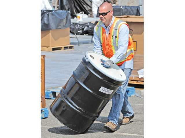 Clean Harbor project manager Eric Brown rolls a barrel to be filled with hazardous materials, such as car batteries, motor oil, brake fluid and pesticides, which were dropped off for recycling by hundreds of vehicles in the upper parking lot of College of the Canyons in Valencia on Saturday.