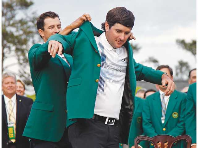 Defending Masters champion Adam Scott, left, helps Bubba Watson, right, with his green jacket after Watson won the Masters on Sunday in Augusta, Ga.