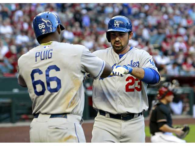 Los Angeles Dodgers' Adrian Gonzalez (23) is congratulated by teammate Yasiel Puig (66) after hitting a two-run home run against the Arizona Diamondbacks on Saturday in Phoenix.