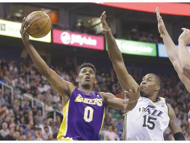 Los Angeles Laker Nick Young (0) lays the ball in as Utah Jazz center Derrick Favors (15) defends in the second quarter on Monday in Salt Lake City.
