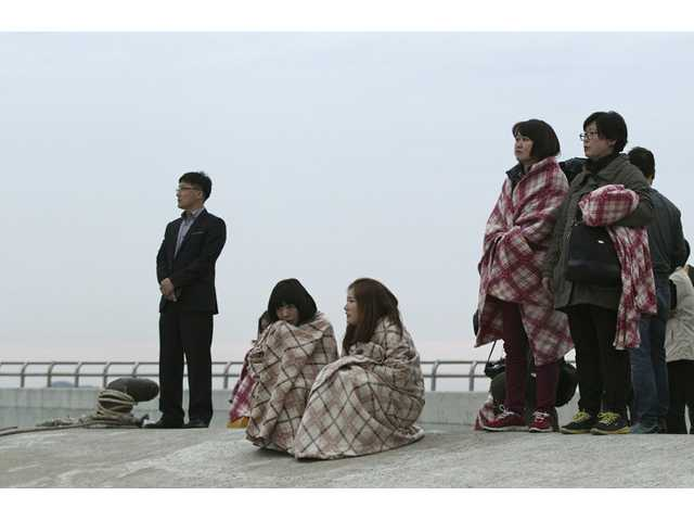 Relatives wait for their missing loved ones at a port in Jindo, South Korea on Wednesday.