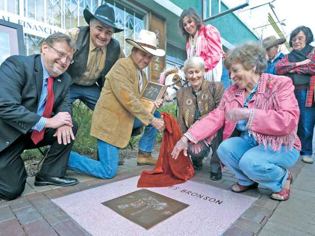"Members of the Santa Clarita City Council look on as actor Martin Kove, third from left,  who appeared in the 1977 movie ""The White Buffalo"" with inductee Charles Bronson unveils Bronson's star on the Walk of Western Stars on Main Street in Newhall Thursday evening. Signal photo by Dan Watson."