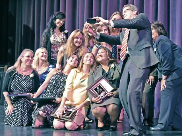 "Superintendent Dr. Marc Winger, right, takes a ""selfie"" photo with the Newhall School District teacher honorees on stage at the 30th Teacher Tribute held at College of the Canyons on Wednesday. Signal photo by Dan Watson."