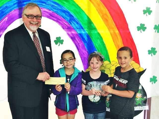 Mark Young, Bridge to Home board member, receives a check for over $2,000 from representatives from the winning 2nd grade. Courtesy photo