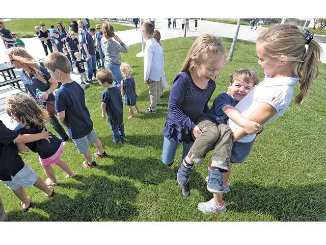 "Tori Hughes, 6, left, and her sister Lexy, 9 carry their brother Liam, 4, to line up for a ""family photo"" in Stevenson Ranch on Friday as they join a group of an estimated 60 of the 120 West Ranch High School babies that have been born to faculty, teachers and administration since the school was started 10 years ago in Stevenson Ranch."