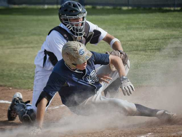 Saugus' Rex Kemple, right, scores a run past Golden Valley catcher Jordan Garrett during Friday's game at Golden Valley High School.