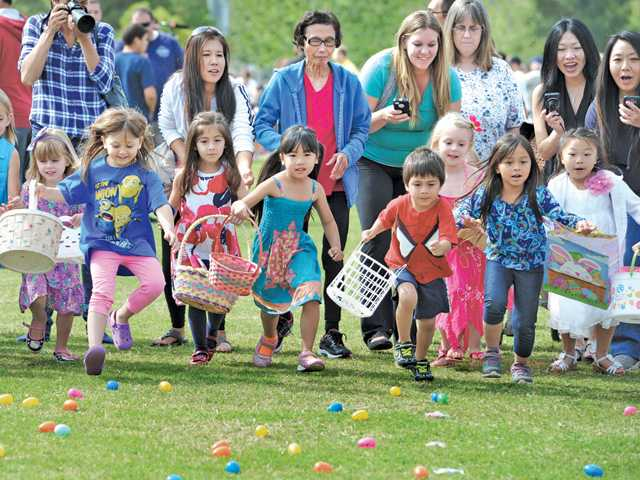 Some of the estimated 1500 children caring their Easter egg baskets dash forward to pick up some the 25,000 plastic eggs containing prizes, toys and candy at the Eggstravaganza event at Central park in Saugus on Saturday. Signal photo by Dan Watson.