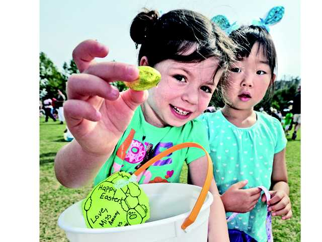 Jordan Metzger, 4, left, and friend Charlotte Lee, 5, display some the treats they gathered along with an  estimated 1,500 children who participated in the Eggstravaganza event where children picked up more than 25,000 plastic eggs containing prizes, toys and candy at Central park in Saugus on Saturday.
