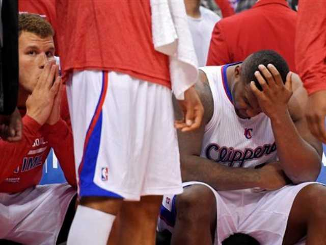 Los Angeles Clippers' Blake Griffin, left, looks on from the bench as Glen Davis rubs his head during the second half in Game 1 of an opening-round NBA basketball playoff series, Saturday, April 19, 2014, in Los Angeles.