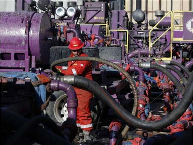 This March 25, 2014 file photo shows a worker adjusting hoses during a hydraulic fracturing operation at an Encana Corp. gas well, near Mead, Colo.
