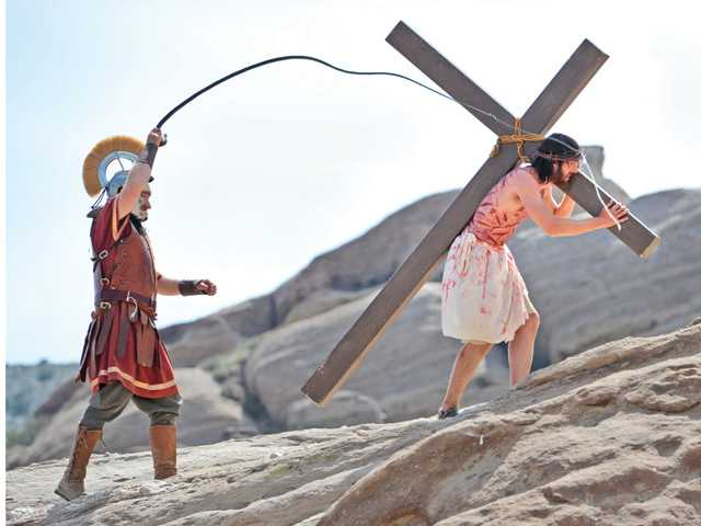Roman Centurion, left, played by Joel Sheridan, whips Moore as he carries the cross to his crucifixion before a crowd of hundreds.