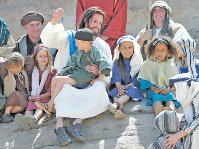 "Jonathan Moore, center, portraying Jesus Christ, calls the children to him during the ""Sermon on the Mount"" in the Easter Sunrise passion play ""A Living Hope,"" presented at Vasquez Rocks Natural Area Park in Agua Dulce on Saturday afternoon."