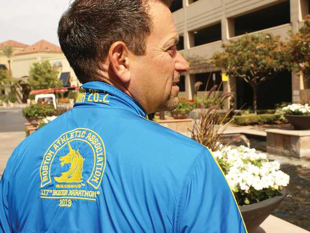 Dennis Lebman wears a jacket he received for participating in last year's Boston Marathon. The SCV resident is back on the streets of Boston today to run again. Signal photo by Jim Holt.