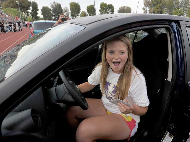 Valencia High School junior Taylor Morrison turns the winning key to her brand new 2014 Nissan Versa during Monday's Nissan car giveaway raffle at College of the Canyons. Signal photo by Charlie Kaijo.