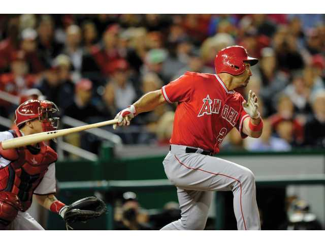 Los Angeles' Raul Ibanez follows through on his double that drove in three runs during the eighth inning of Monday's game against the Nationals in Washington.