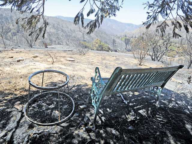 A burned bench looks out on the charred acreage behind a Lake Hughes home in June 2013, part of the damage left in the wake of the Powerhouse Fire. Signal file photo