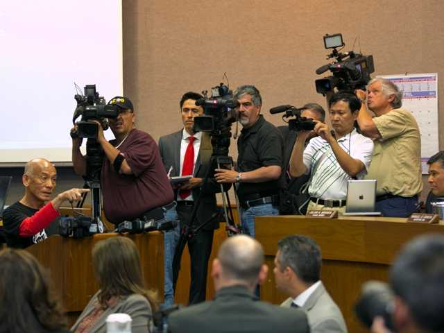Sriracha hot sauce founder David Tran, at podium, left, addresses a city council meeting in Irwindale. The city is suing Sriracha declaring it public nuisance over odors emitted from the plant.