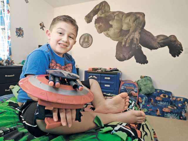 Richie Gonzales, 7, plays with his Captain America shield in his superhero-themed bedroom. The Incredible Hulk, seen on the wall, is among his favorite superheroes. Signal photo by Dan Watson