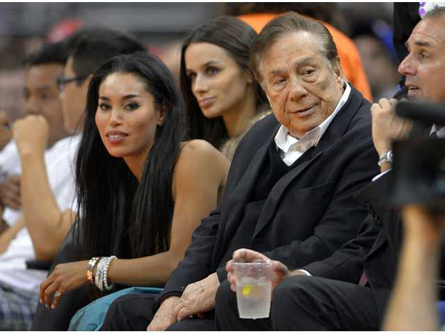 In this photo taken on Oct. 25, 2013, Los Angeles Clippers owner Donald Sterling, right, watches a Los Angeles Clippers game in Los Angeles.