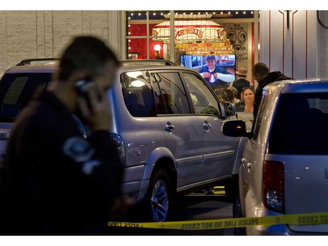 Police investigate a fatal parking lot accident in which a man in his 70's driving an SUV lost control and drove into a line of people waiting to enter Farrell's Ice Cream Parlour in Buena Park on Friday.