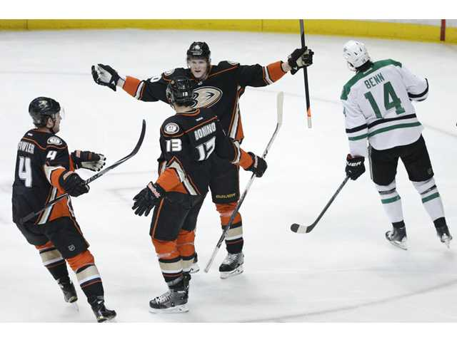 Anaheim's Nick Bonino(13) celebrates his goal with Cam Fowler(4) and Corey Perry(10) as the Stars' Jamie Benn(14) skates past them in the first period of Friday's Game 5 in Anaheim.