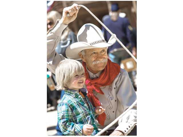 3 year-old Charlie Reds of Los Angeles, left, with trickroper David Thornbury at the 21st annual Santa Clarita Cowboy Festival at the Melody Ranch Motion Picture Studio Saturday.