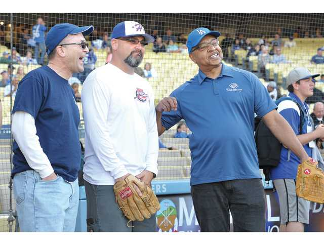 From left, The Santa Clarita Valley Signal Executive Editor /Supervising Producer Jason Schaff, Arnie Durazo President Hart Pony League and retiring Boys and Girls Club of Santa Clarita Valley Chief Professional Officer Jim Ventress prepare to throw the ceremonial first pitch of the game on Saturday evening.