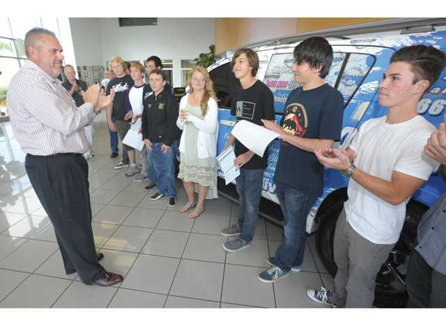 Nissan of Valencia executive manager Dan Sterkel, left, presents William S. Hart Union High School District students who had attendance records of 97 percent or higher with gifts, scholarships and a car, totaling $21,800 on Saturday.