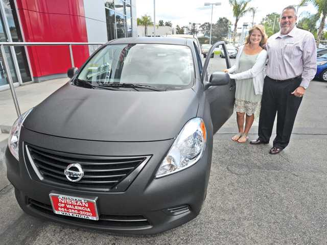 Valencia High School junior Taylor Morrison receives a 2014 Nissan at the giveaway, created by the dealership, in partnership with district officials, to encourage students to stay in school.