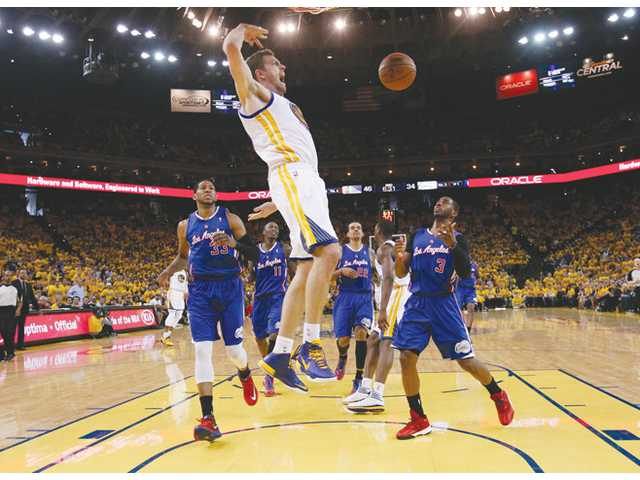 Golden State Warriors' David Lee, center, dunks against the Los Angeles Clippers on Sunday in Oakland.