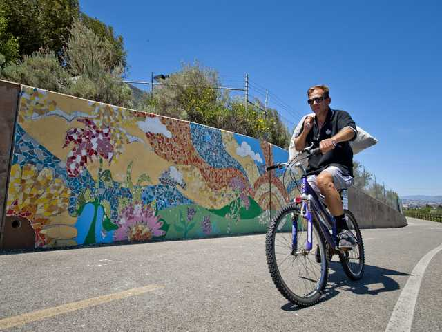 A biker rides past a mosaic install last weekend by community volunteers and The ARTree Community Arts Center. A second round of construction will occur this weekend. Signal photo by Charlie Kaijo