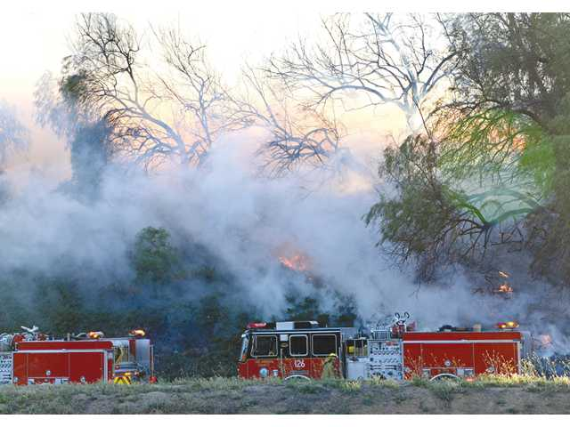 Fire crews work to knock down a quarter-acre brush fire alongside the south-bound Interstate 5 at McBean Parkway Tuesday evening.