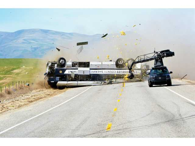 The specially fitted Cadillac Escalade camera car films a bus flip over for a movie.