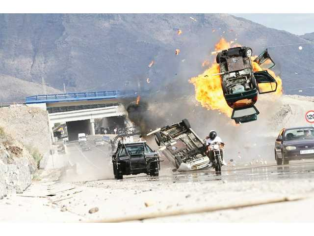 "A black, outfitted camera car in the middle of the action films a motorcycle chase and crash from the movie the ""Fast & Furious 6."""