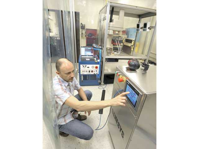 Vice President of Engineering Liviu Marian programs the generator of the CO2 robotic sprayer in the CleanLogix lab in Valencia.