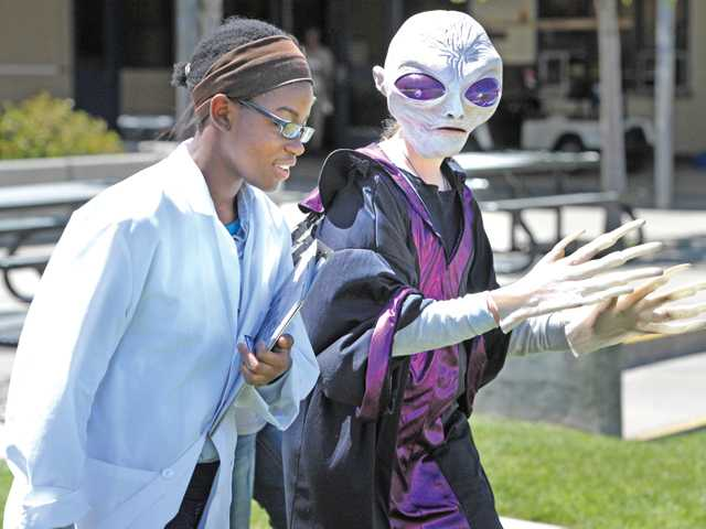 "Eighth grader Ehinomen Edo, left, medical officer, wears a lab coat as she walks with Sierra Cottrell,  a ""freindly alien"" to where a mock moon walk will take place during the Shuttle Simulator Project at Ranch Pico Junior High School in Stevenson Ranch on Wednesday, Signal photo by Dan Watson."