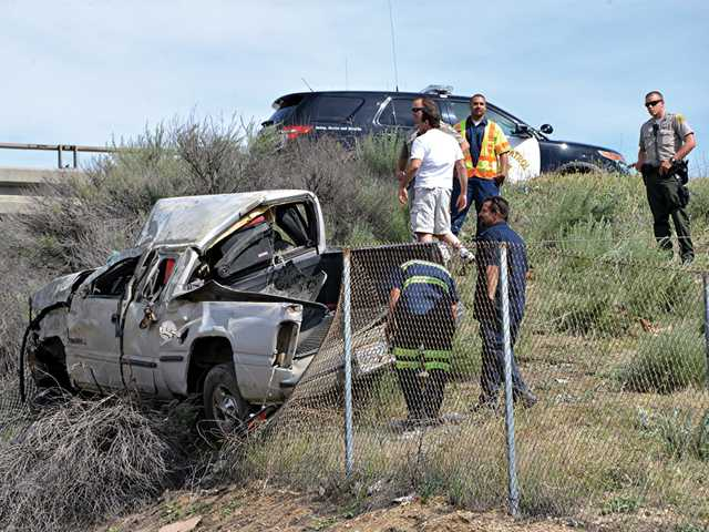Emergency responders survey the crash site after a truck crashed on an embankment off Highway 14 at Newhall Avenue on Thursday, trapping a man inside. Photo courtesy of Rick McClure.