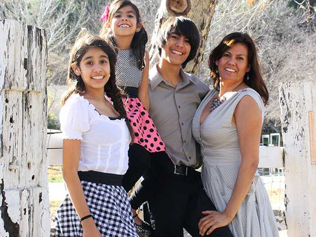 Morelia, 12, Mariposa, 7, and Moises, 15, with their mother Miriam December 2013. Courtesy Photo