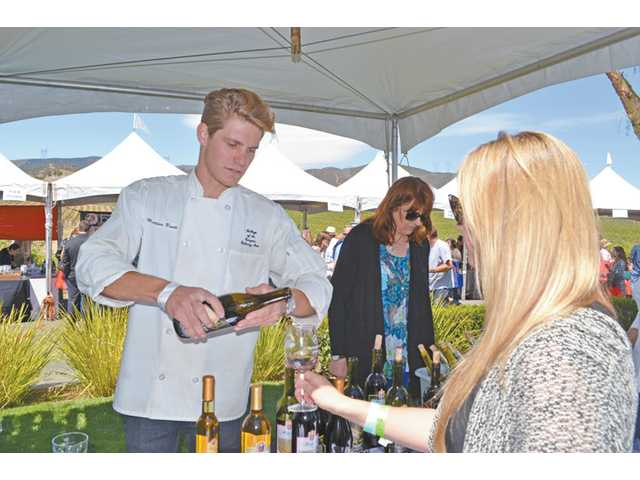 Matthew Booth, left, member of the College of the Canyons Culinary Arts program, pours wine for Valencia resident Keelan Moon.