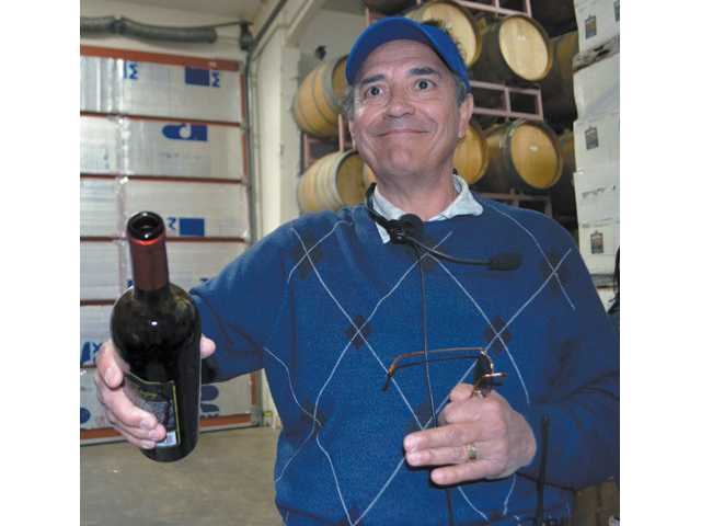 Reyes Winery owner Robert Reyes pours his syrah during a tour of his vineyard and winemaking facilities.