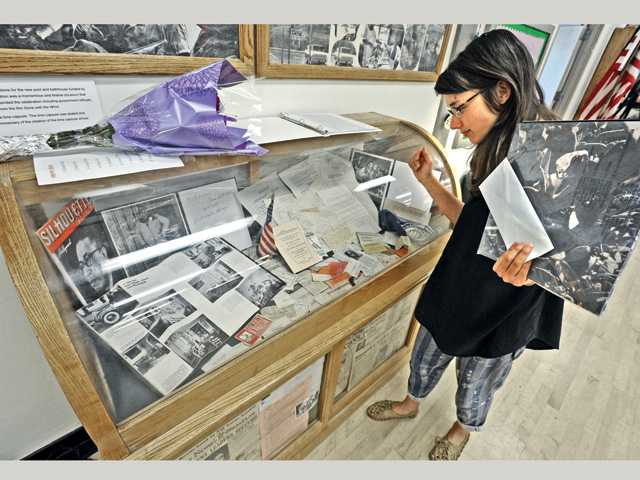 Val Verde resident Susanna Battin examines artifacts from a time capsule buried in 1939 as the cornerstone of the Val Verde swimming pool, which was unearthed in 1994.